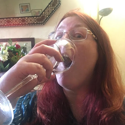 A redheaded white woman pouring a glass of wine into her mouth
