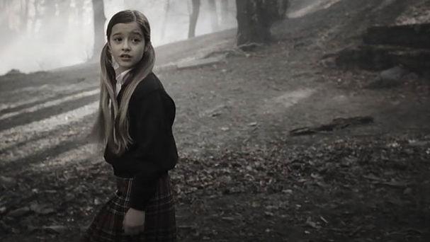 fotograma con la pequeña protagonista Alicia en la tenebrosa arboleda