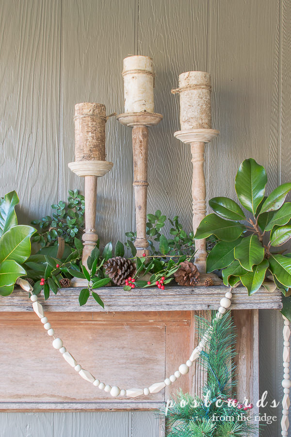 outdoor Christmas mantel with rustic wood candlesticks and birch pillar candles
