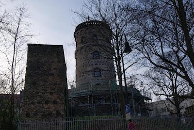 Ein kreisrunder Turm, welcher auf einer Anhöhe steht. Die Ahnhöhe ist von einem Baugerüst umgeben. Rechts daneben ein altes Stück Mauer.