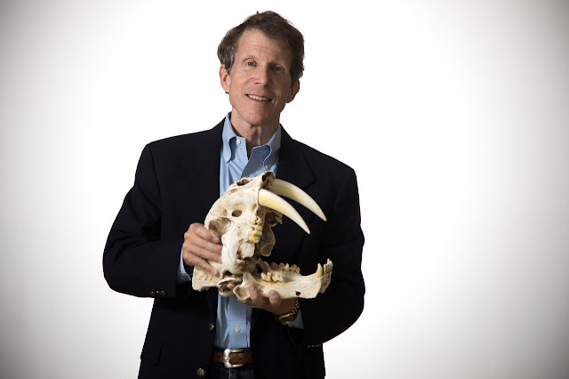 Dr. Neil Bockoven, author of Moctu and the Mammoth People, holds a saber-toothed cat skull