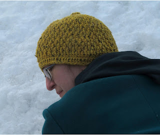 A woman wearing a crochet hat done in the textured alpine stitch