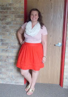 an outfit with a white lace scarf, pink tee, red skirt, and gold sandals