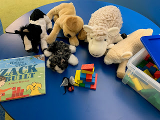 The House that Zack Built picture book lying next to farm animal puppets (cow, dog, sheep, cat, fly) and blocks on top of a table