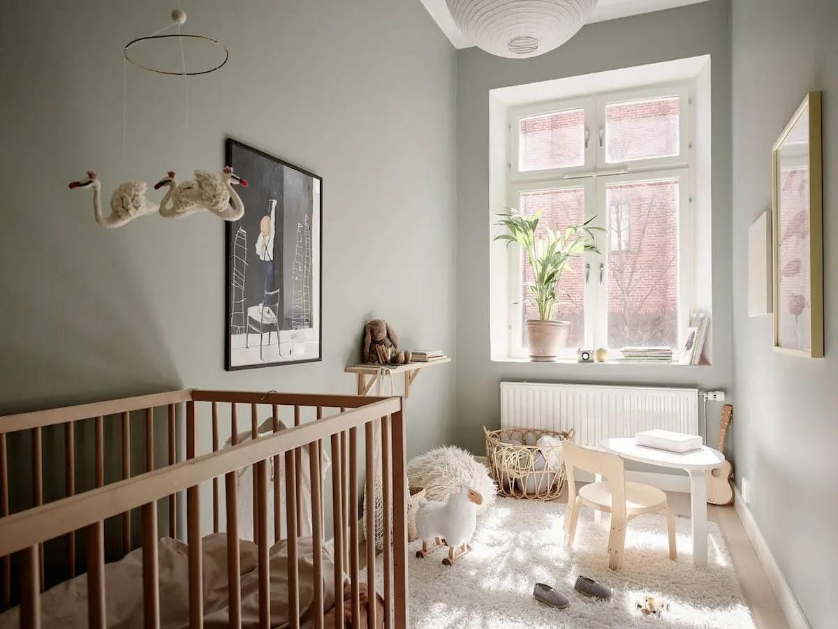 Dormitorio infantil pintado de verde claro con muebles de madera