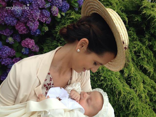 Look invitada con vestido de mariposas, chaqueta beig y canotier Luanco en burdeos, fondo de flores de hortensia y un bebé en brazos, con recogido bajo de trenzas