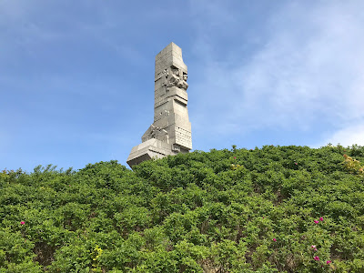tall monument behind some trees under a blue sky