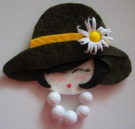 rosto de daminha em feltro com chapéu e margarida