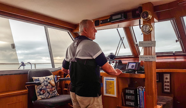 Photo of Phil at the helm of Ravensdale at sea