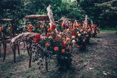 Decoración del pasillo nupcial con abundantes flores en un espacio natural