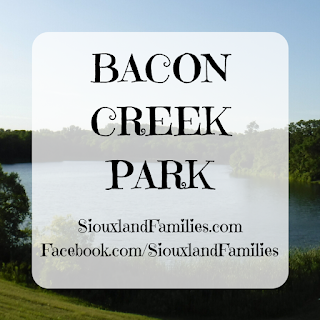 "in background, a small lake sits below a grassy hill, with a small forested area visible on the opposite shore. in foreground, the words ""Bacon Creek Park"" and ""SiouxlandFamilies.com Facebook.com/SiouxlandFamilies"