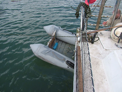 Dinghy half trapped under catamaran on water