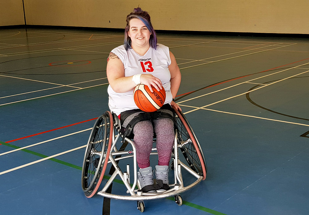 Beth is sat in a silver basketball wheelchair. She is wearing a white vest with the number 13 on it, grey and burgundy leggings and grey trainers. She is holding a ball on her lap and has a big smile on her face