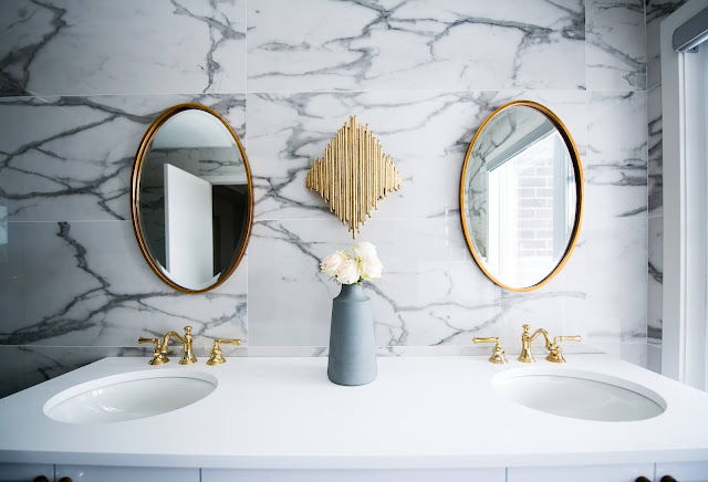Twin sinks with gold accessories and mirror