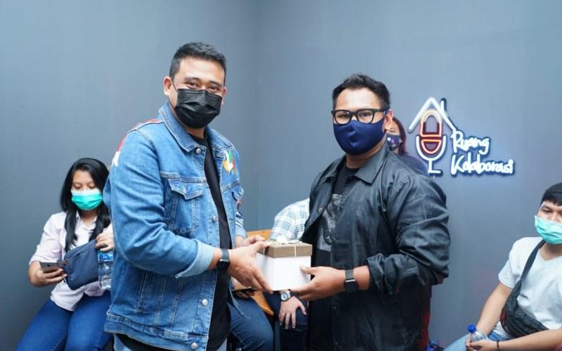 Bobby Nasution menyerahkan hadiah kepada pemenang lomba desain baju official tim pemenangan , Ihza Mahendra di Ruang Kolaborasi Media Center Jalan Cik Ditiro Medan, Senin (26/10/2020).