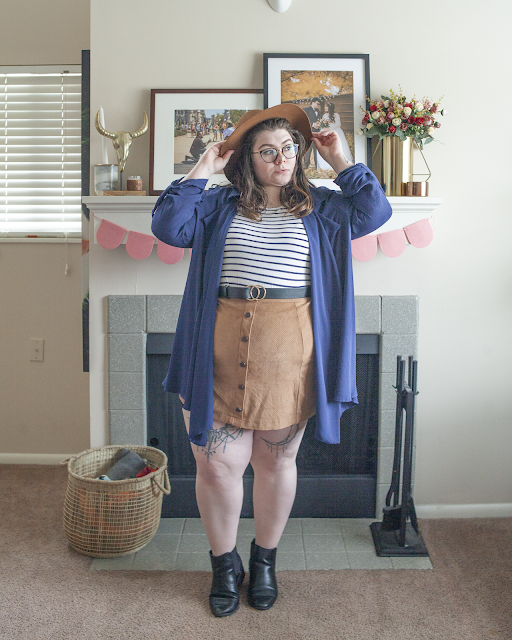 An outfit consisting of brown panama hat, navy blue structureless trench coat, striped tee tucked into a brown mini skirt and black chelsea boots.