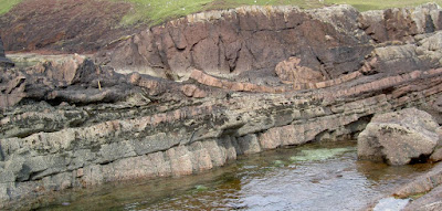 "A field photo take at Stoer showing the laminar beds of sandstone in the bottom of the picture. In the middle is the impact deposit (12m thick at this location) that contains ""rafts"" of deformed pink sandstone. Credit: Ken Amor / Department of Earth Sciences"