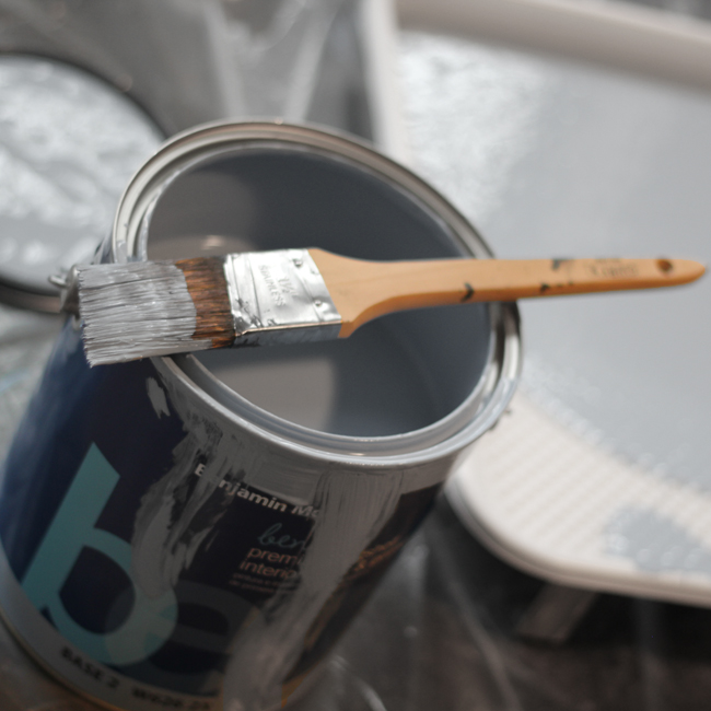 Can of gray paint with paint brush