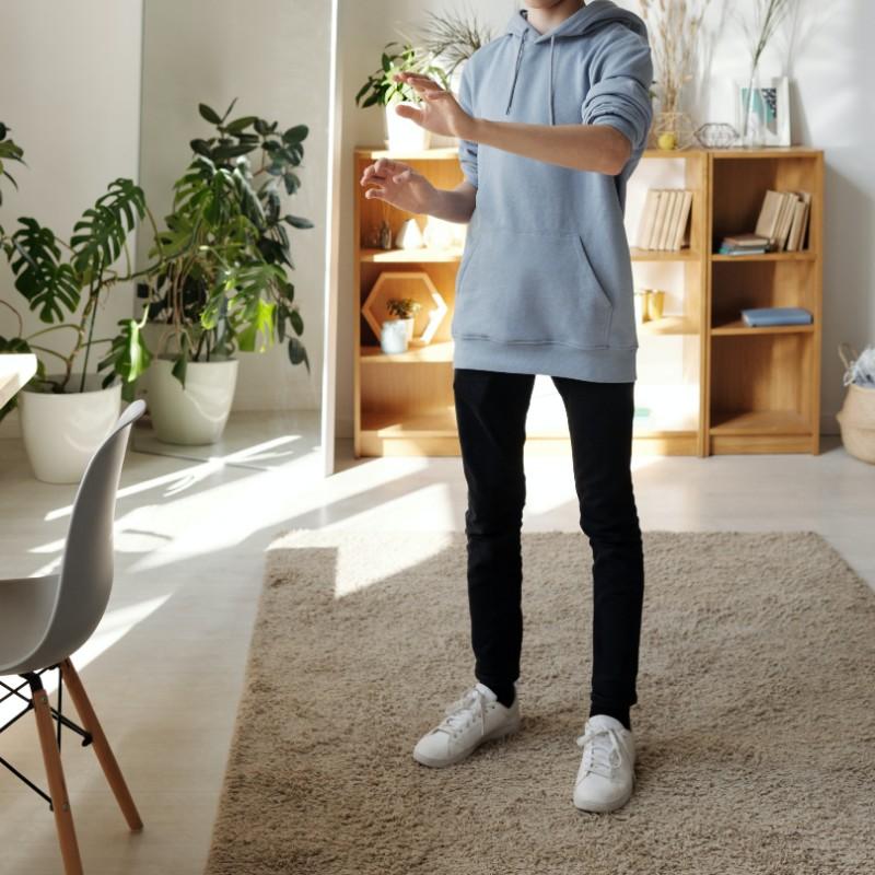A teen boy standing at home.