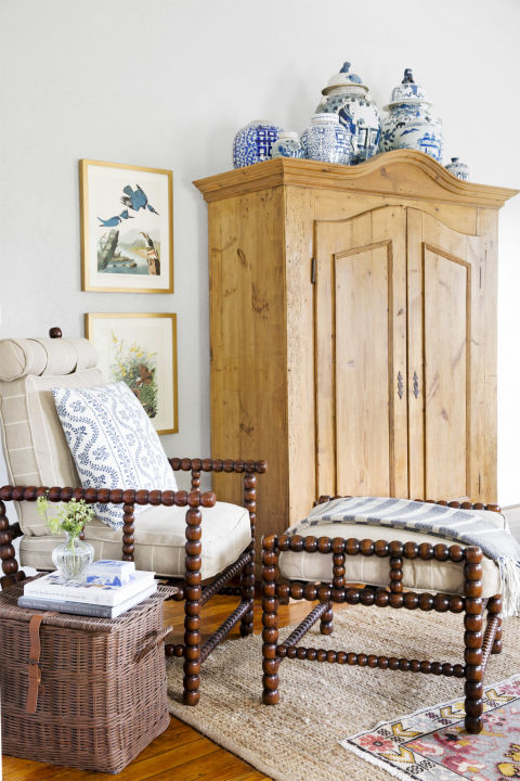 Living room decor with farmhouse style in a charming cottage. Wood spindle chair has blue accents, and a rustic pine armoire nearby holds blue and white porcelain. Interior design by Holly Mathis. #livingroom #farmhouse #cottagestyle #decorating