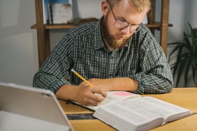 A man studying the bible with notes besides