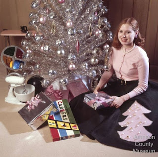 Young woman sitting by an aluminum tree with lots of presents and a color wheel under it.