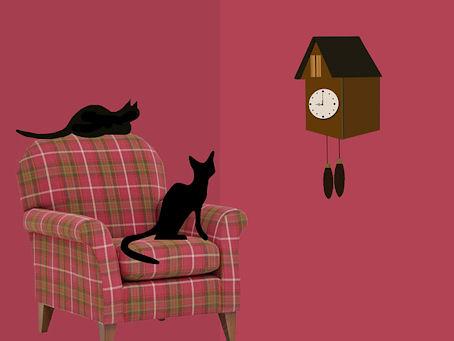 Piirroskuvassa kaksi mustaa kissaa tuijottelevat seinällä olevan kellon taulua.