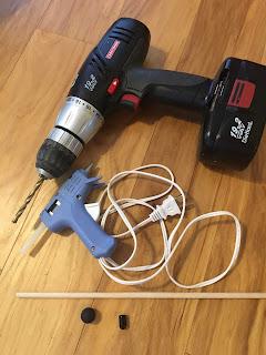 Drill, glue gun, wooden dowel, rubber paintball, vinyl end cap