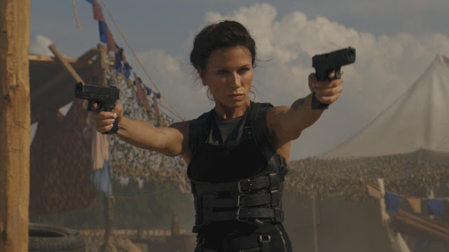 Rhona Mitra with two guns