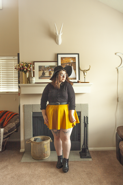 An outfit consisting of an oversized black floppy hat, a black long sleeved collared blouse with a studded collar tucked into a mustard yellow mini skater skirt, and black Chelsea boots.