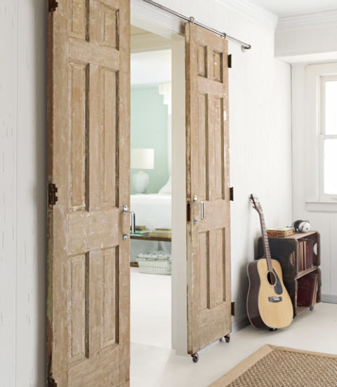 a couple of vintage doors are transformed into a barn door