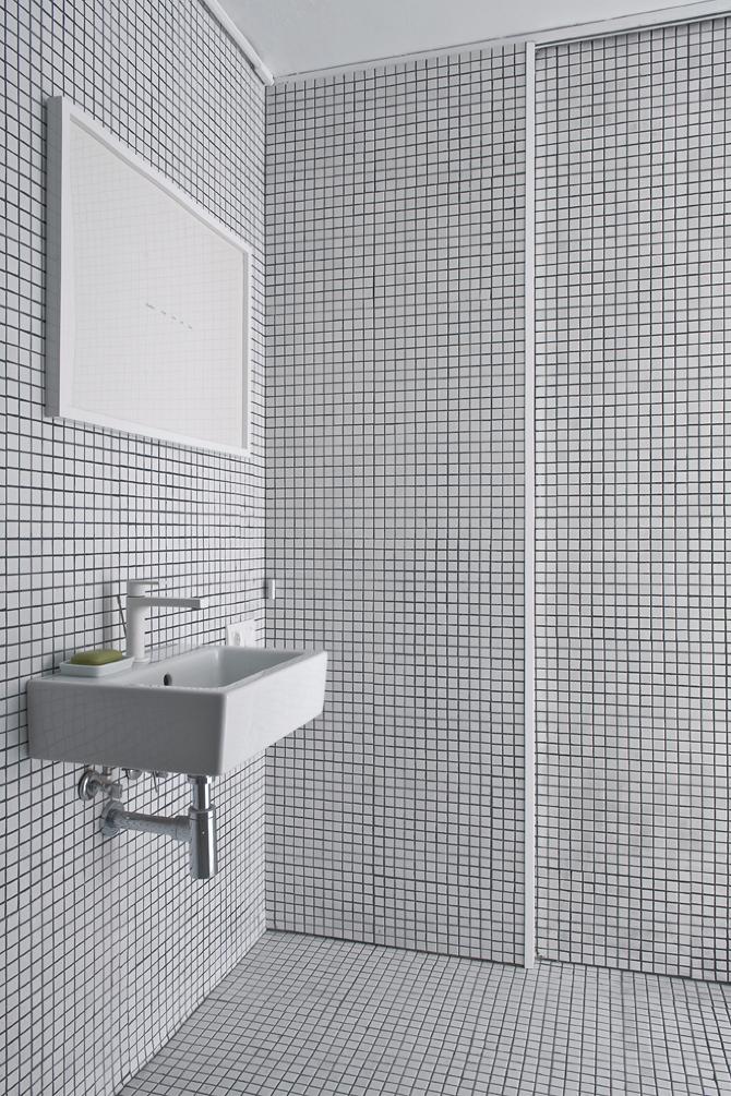 Cuarto de baño minimalista con pequeños azulejos blancos y negros