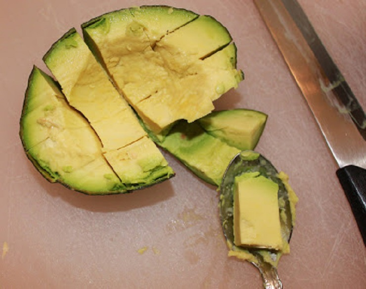 slicing avocado into cubes with a knife