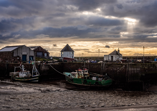 Photo of fishing boats in the entrance to Maryport Harbour at dusk