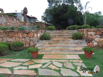 Execução do caminho no jardim com pedra Goiás com juntas de grama com execução da escada de pedra Goiás serrada com execução do paisagismo em residência em Piracaia-SP.