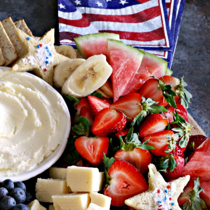 Patriotic themed charcuterie board with red, white and blue fruit and star shaped cookies.