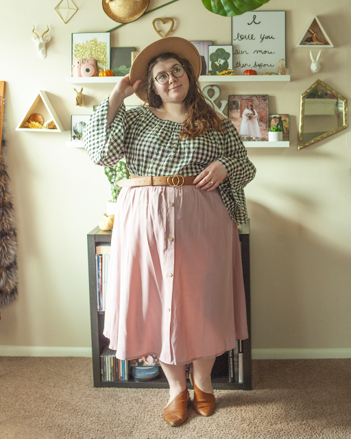An outfit consisting of a wide brim camel brown hat, an off the shoulder white and black gingham blouse with bell sleeved tucked into a button down pink midi skirt, belted with a camel brown belt and cognac brown d'orsay flats.