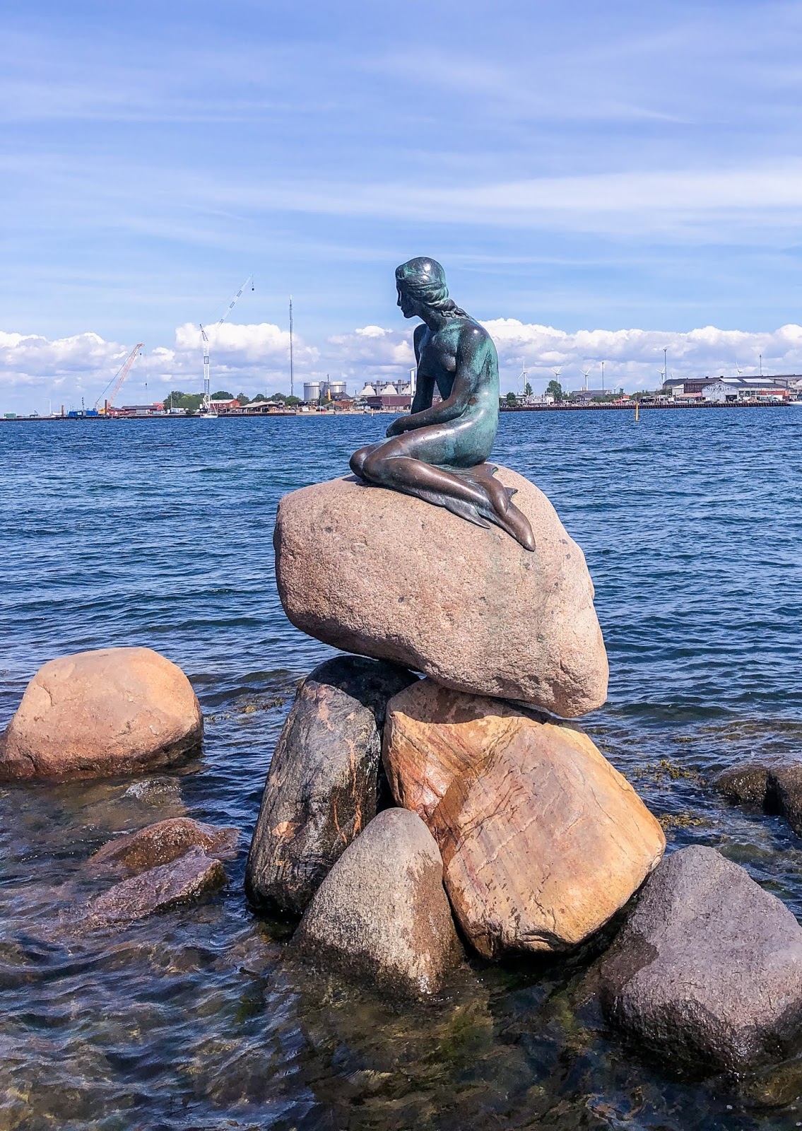 the little mermaid statue in Copenhagen on rocks against blue water and sky