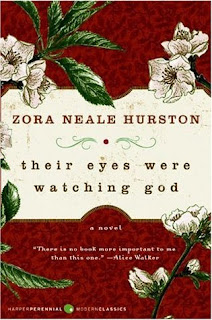 "A white card with ""ZORA NEALE HURSTON"" above ""their eyes were watching god"" is framed above and below by a red background with white flowers."