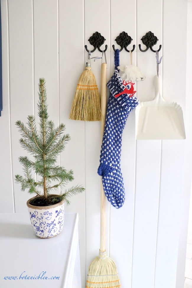 Blue Christmas Laundry Room decorated early with potted trees and blue and white knit stocking