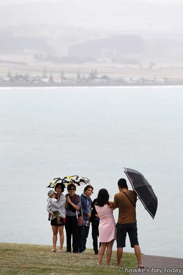 People shelter under umbrellas at the Bluff Hill Lookout, Napier, looking over Hawke Bay towards Westshore and Poraiti, in wet weather, a little bit of rain. photograph