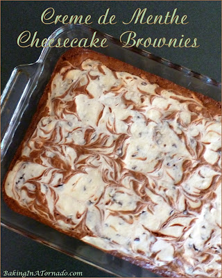 Crème de Menthe Cheesecake Brownies are a gooey chocolate treat. Studded with chocolate crème de menthe baking chips and swirled with a cheesecake layer, these brownies are a family favorite. | Recipe developed by www.BakingInATornado.com | #recipe #dessert
