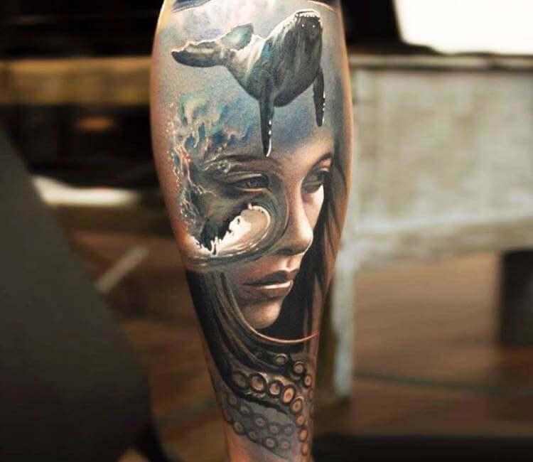 Tatuaje de un rostro en el fondo del mar con una ballena
