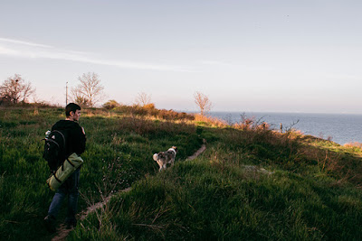 A person carrying a backpack walks along a narrow path behind a dog through green grass