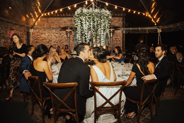bride and groom kiss during dinner