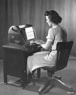 A black and white photograph of a woman seated at a desk and typing.