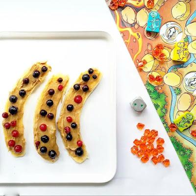 Rodajas de plátano cubiertas con crema de cacahuete y arándanos junto al juego diente de dragón