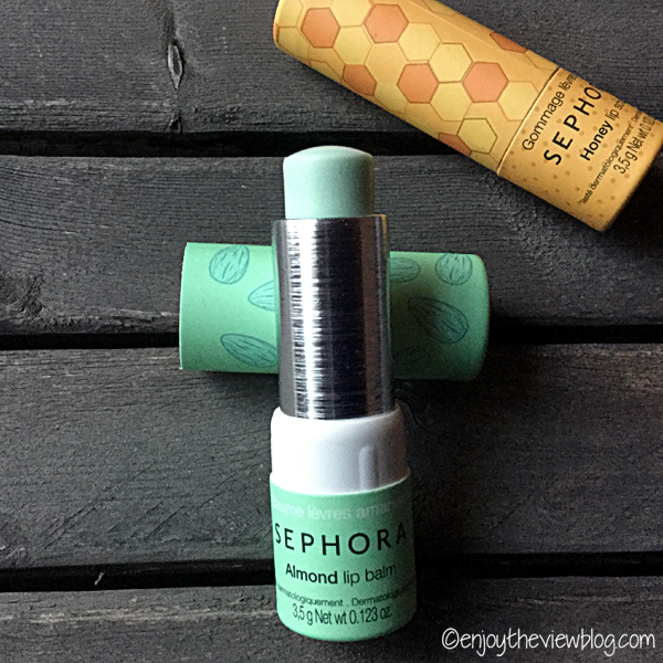 An open tube of Sephora Almond Lip Balm lying on a wooden table with a tube of Sephora Honey Lip Scrub in the background