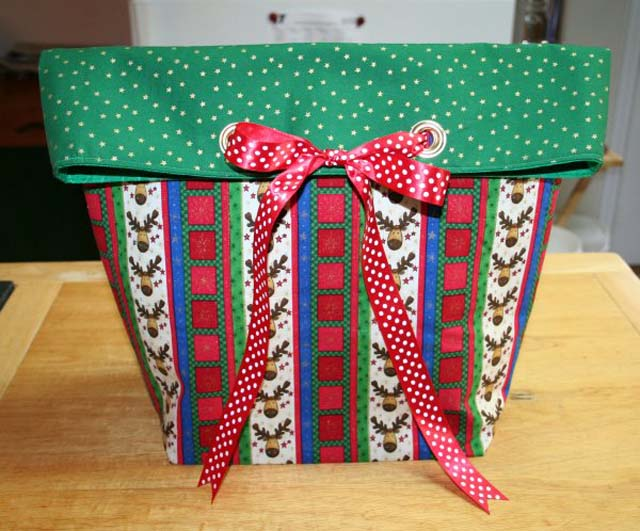 Learn how to make a reusable fabric gift bag with a bow and grommets. Tutorial by Super Mom No Cape!