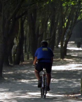 homem pedalando no parque
